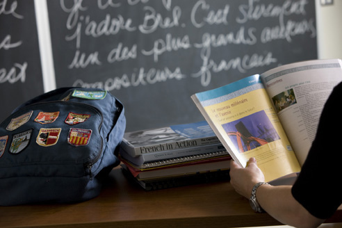 French Class, Student at Desk Reading with Books and Backpack
