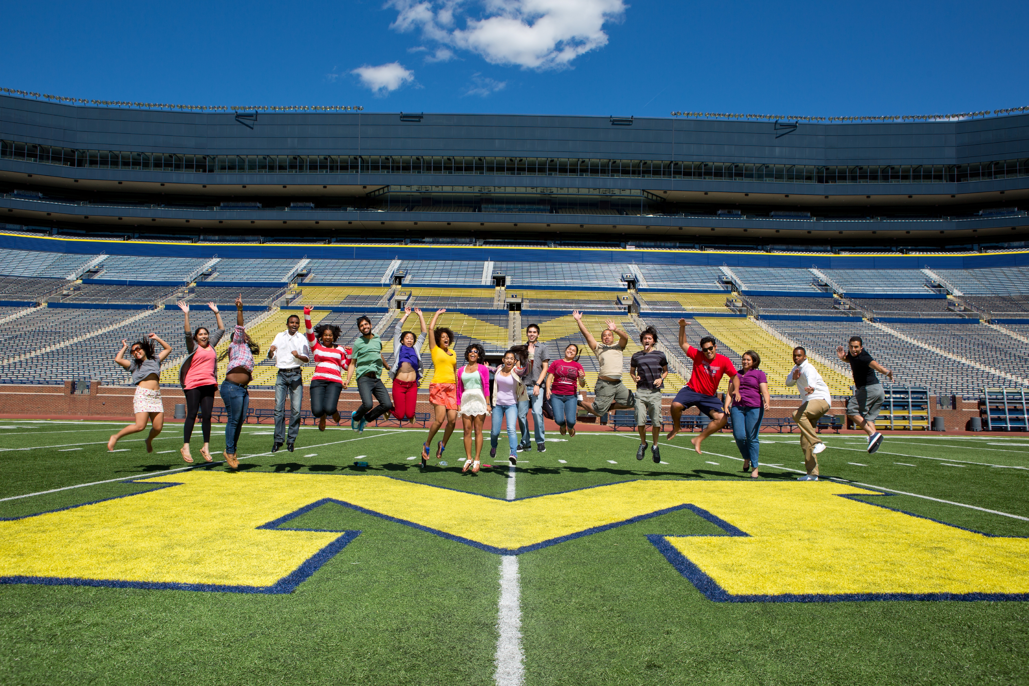 A group of students jumping simultaneously on the Michigan field in the Big House.