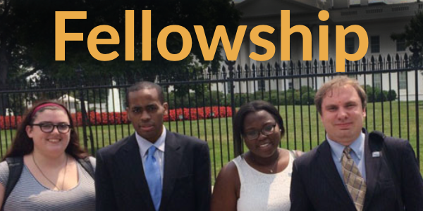 Four students with arms around each other in front of White House