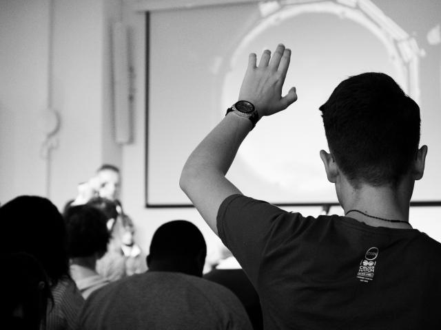 Black and white photo of a young man raising hand