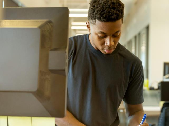 Young Black Man standing at a computer taking handwritten notes in a library