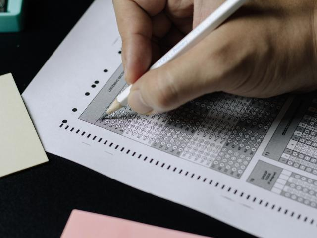 Image of Scantron Bubbles being filled in by a white male hand holding a pencil