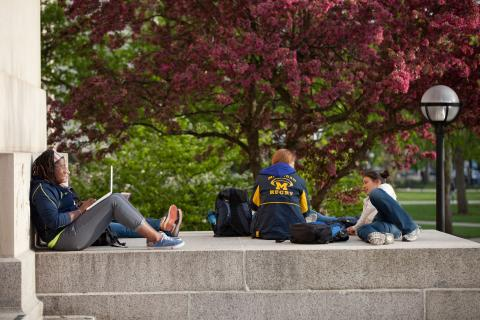 Students sitting on steps in front of Angell Hall