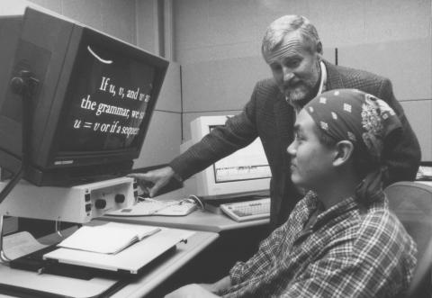 Black and White Photo of a college-aged Asian man with a bandana tied around his forehead, sitting at a computer, whose screen has mathematical symbols on it. Behind the young man an older gentleman stands smiling with a hand on the computer monitro